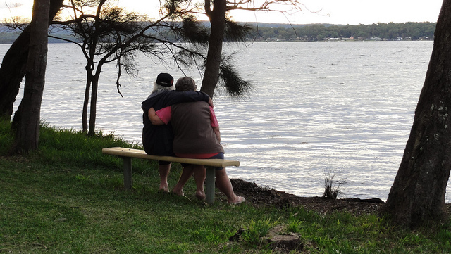Friends hugging on a bench in Jervis Bay, NSW, Australia