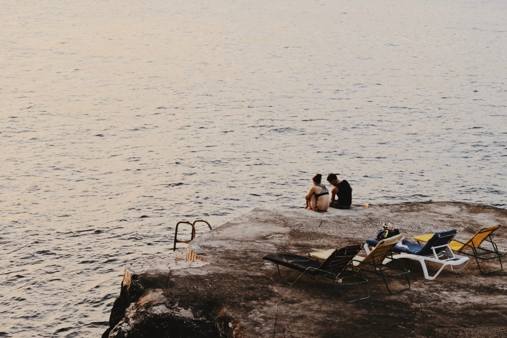 Two people sitting on a beach bluff in Negril Jamaica