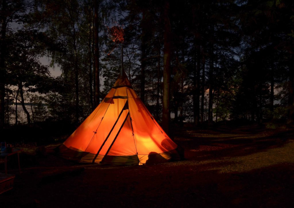 Orange camping tent lit up at night in the dark wilderness