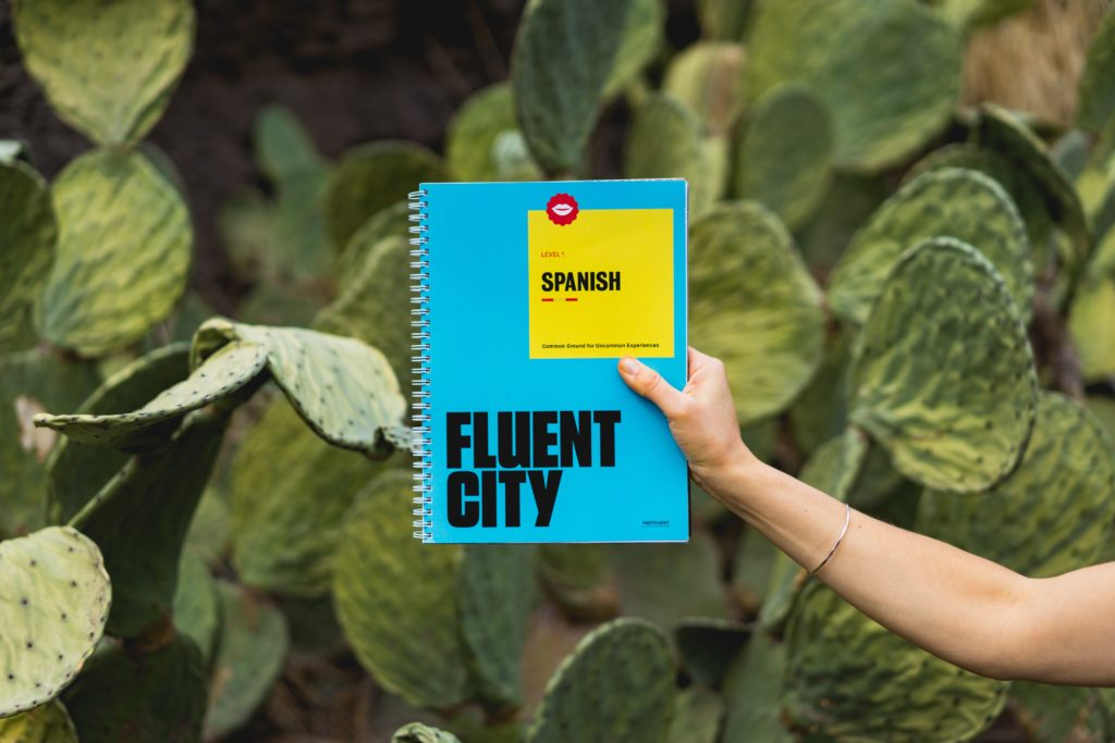 Person holding a Fluent City Spanish hand book in front of a cactus