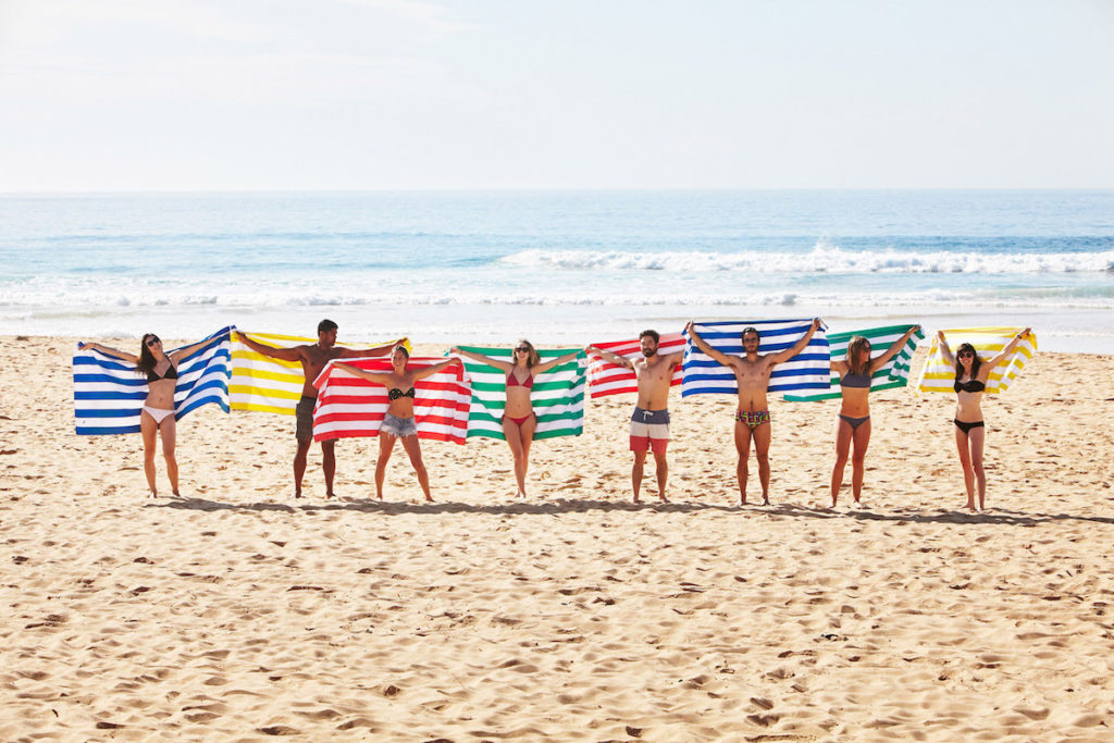 People holding up their colorful dock and back towels on the beach