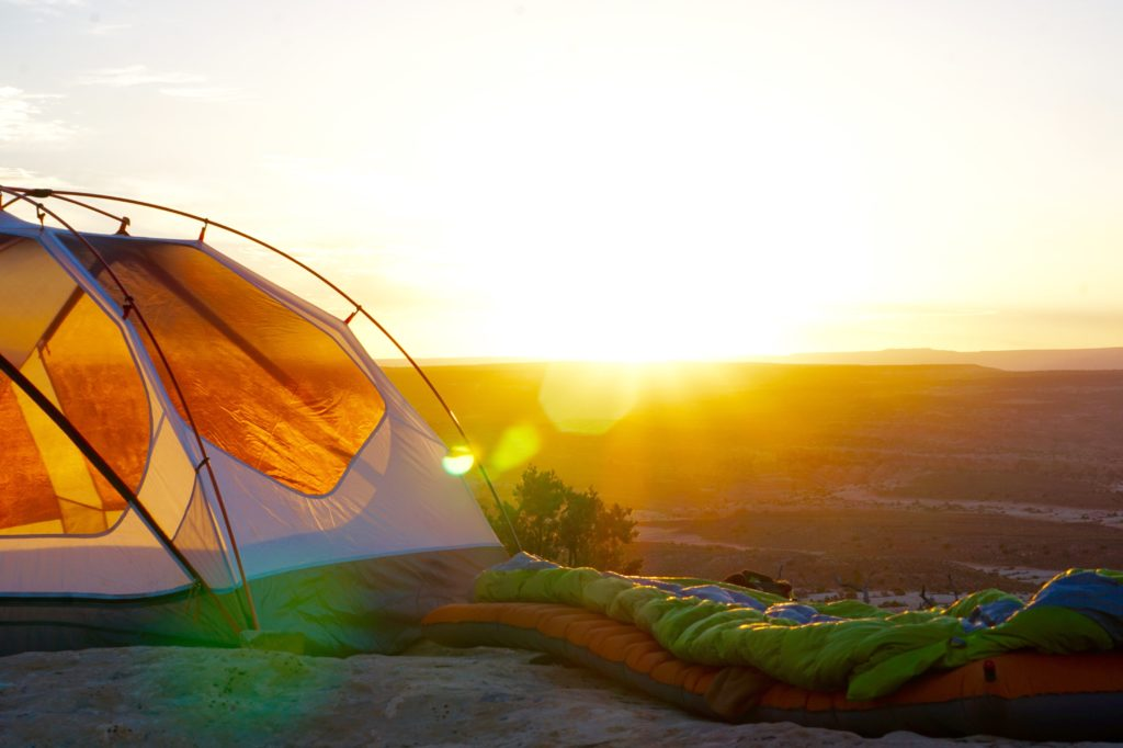 Sleeping bag and pad next to a tent at sunrise