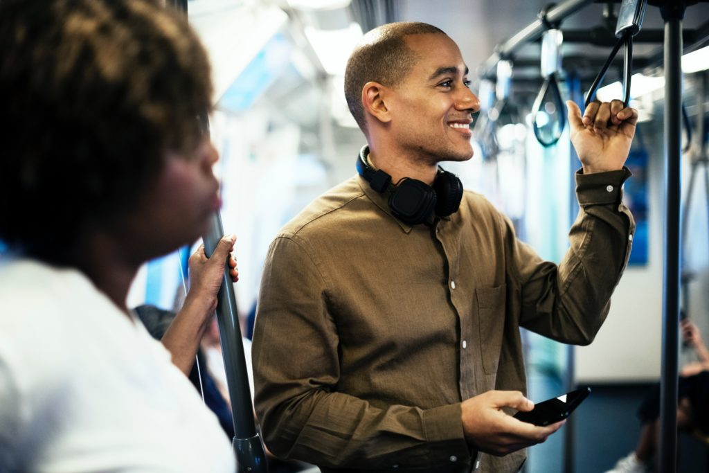Man on public transport with wireless headphones